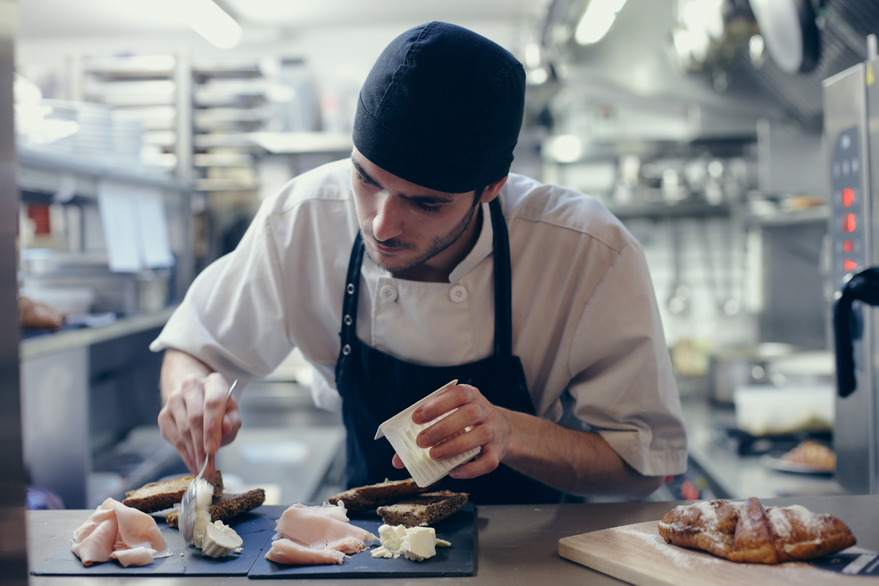 Cook preparing a plate with ham cheese and bread