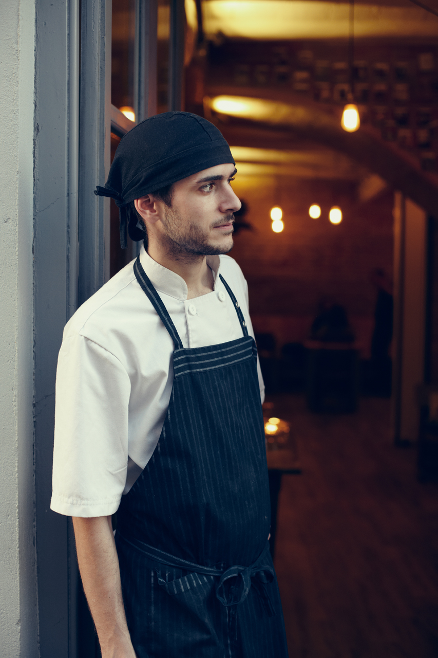 Portrait of a cook at the front door of the restaurant