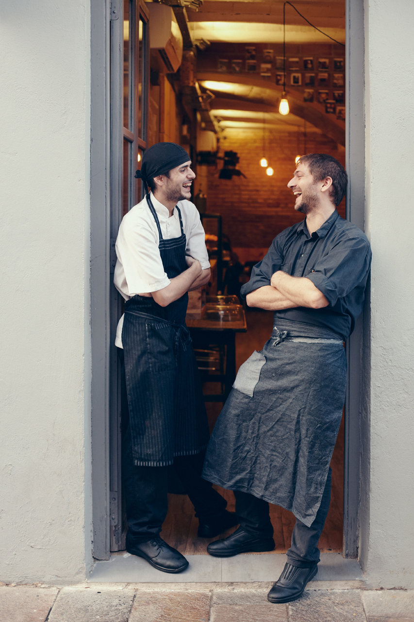 Two cooks laughing together at the door of the coffee shop