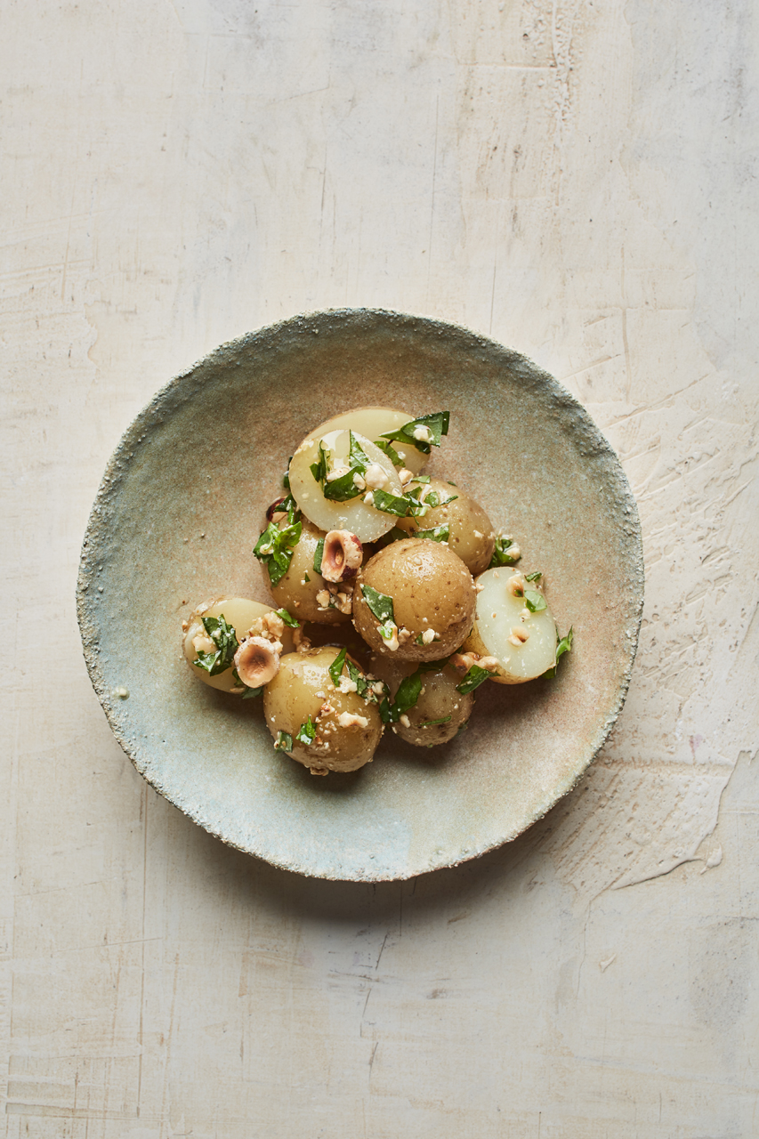 Potatoe salad with hazelnuts, pinenuts and green leaves